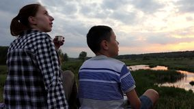 Young woman and a boy look at sky with their drone at a lake. An impressive view of a young woman and a boy who sit on a lake bank covered with grass and look at stock video