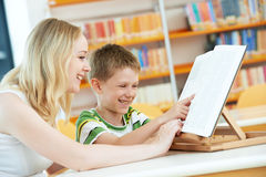 Young woman and boy reading book in library Stock Photography