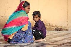 Young woman and a boy sitting at Karni Mata Temple, Deshnok, Ind Stock Images