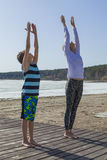 Young woman and boy stretching hands to the sky Stock Images