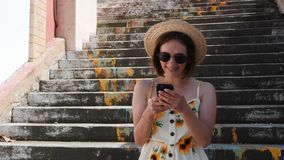 Young woman with braces in straw hat and black sunglasses standing on steps with phone in hands and smiling
