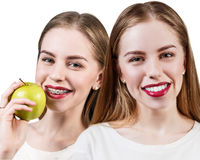 Young woman with brackets on teeth eating apple Stock Photo