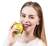 Young woman with brackets on teeth eating apple Royalty Free Stock Images