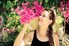 Young woman with braid smelling pink flowers Stock Image