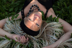 Young woman with braided lies on the grass Stock Image
