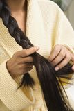 Young woman braiding hair. Close up of Asian/Indian young woman braiding hair Royalty Free Stock Image