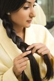 Young woman braiding hair. Stock Photo