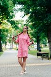 Young woman with braids in a summer park in pink clothes in summer outdoors Royalty Free Stock Photo