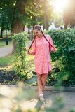 Young woman with braids in a summer park in pink clothes in summer outdoors Royalty Free Stock Photos