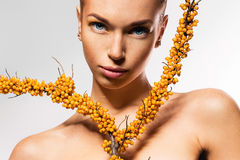 Young woman and branch of sea-buckthorn Royalty Free Stock Images