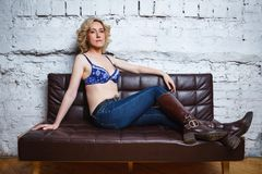 Young woman in brassiere sits on sofa. Young sexy woman in brassiere sits on sofa royalty free stock photography