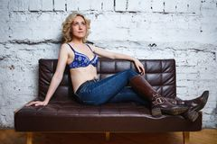 Young woman in brassiere sits on sofa. Young sexy woman in brassiere sits on sofa stock photography
