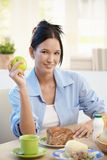 Young woman at breakfast with apple Royalty Free Stock Images