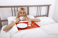 Young woman with breakfast tray in bed Royalty Free Stock Photos