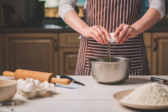 Young woman breaking egg over bowl with dough, close-up Royalty Free Stock Image