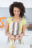 Young woman breaking egg to make cookie dough. Young woman breaking an egg to make cookie dough Stock Photo