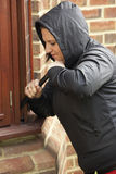 Young Woman Breaking Into House Stock Photography