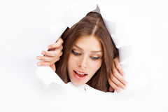Young woman breaking through a paper sheet Stock Photos