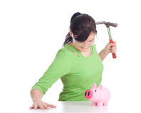 Young woman breaking a piggy bank Royalty Free Stock Photos