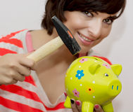 Young woman breaks a porcelain piggy bank with a hammer Royalty Free Stock Photography