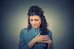Young woman with breast pain touching chest. Closeup portrait young woman with breast pain touching chest isolated on gray wall background Royalty Free Stock Photos