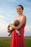 Young woman breastfeeding her baby. Young women breastfeeding her baby outdoors Stock Photos