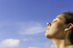 Young woman breathing the fresh air. Closeup of a profile of a young woman breathing the fresh air with her eyes closed with the blue sky background - focus on Stock Photography