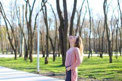 Young woman breathing fresh air in park and relaxing. stock photo
