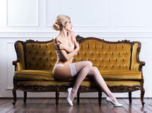Young woman in bridal lingerie on a retro sofa Stock Images