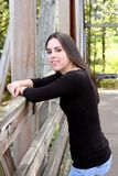 Young woman on bridge. A very pretty teenage girl standing on a wooden bridge royalty free stock images