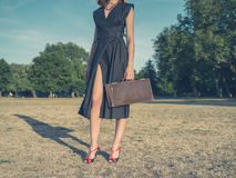 Young woman with briefcase in park Stock Photo