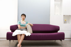 Young woman with briefcase on sofa, portrait Royalty Free Stock Image