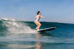 Young woman in bright bikini surfing on a board in ocean royalty free stock image