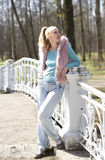 Young woman in bright clothes on the bridge in park Royalty Free Stock Image