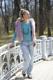 The young woman in bright clothes on the bridge in park in the early spring Stock Photo