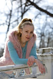 The young woman in bright clothes on the bridge in park in the early spring Stock Photos