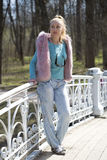 The young woman in bright clothes on the bridge in park in the early spring Royalty Free Stock Images