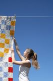 Young woman and bright laundry. Young woman touching a bright patchwork counterpane hanging to dry on a clothes-line royalty free stock image
