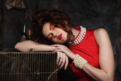 Young woman with bright make-up on a background of theatrical sc. Young woman with bright make-up wearing red dress  on a background of theatrical scenery Royalty Free Stock Photos