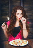 Young woman with bright make up sitting and eating a salad Royalty Free Stock Images