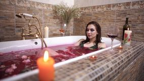 Young woman with bright makeup caress her body lying in the bath with roses and relaxing. Lonely lady made romantic night for herself. Small roses are in red stock footage