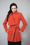 Young woman in a bright orange coat Royalty Free Stock Images