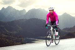 Young Woman in Bright Pink Jacket Riding Road Bicycle on Mountain Alpine Road. Healthy Lifestyle and Adventure Concept stock images