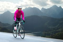 Young Woman in Bright Pink Jacket Riding Road Bicycle on Mountain Alpine Road. Healthy Lifestyle and Adventure Concept. stock image