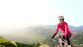 Young Woman in Bright Pink Jacket Riding Road Bicycle on Mountain Alpine Road. Healthy Lifestyle and Adventure Concept. stock photo