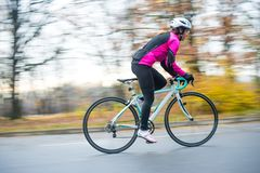 Young Woman in Pink Jacket Riding Road Bicycle in the Park in the Cold Autumn Day. Healthy Lifestyle. royalty free stock photography