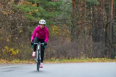 Young Woman in Pink Jacket Riding Road Bicycle in the Park in the Cold Autumn Day. Healthy Lifestyle. royalty free stock photos