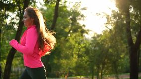 Young woman in bright pink jacket running in the sunny city park exercising outdoors. Steadicam stabilized shot stock video footage