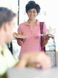 Young woman bringing food and coffee to friend at table in cafe Stock Images