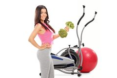 Young woman with a broccoli dumbbell in front of a cross trainer stock photo